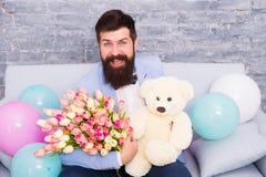 Verzend bloemen als u betekenen het Bloem voor 8 Maart De gebaarde mens met tulpenboeket en draagt De datum van de liefde interna stock foto