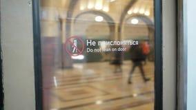 Verzending van metro post Mayakovskaya in Moskou De mening van de glasdeur van de metro met etiket ` leunt niet  stock video