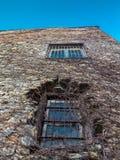 Verzerrte Wand eines alten Steingebäudes mit Fensterscheibe mit zwei Stangen Lizenzfreie Stockfotos