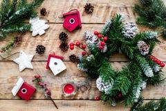 Verzieren Sie Haus für Weihnachten Kranz und Spielwaren auf Draufsicht des hellen hölzernen Hintergrundes Stockfotografie