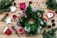 Verzieren Sie Haus für Weihnachten Kranz und Spielwaren auf Draufsicht des hellen hölzernen Hintergrundes Lizenzfreie Stockfotografie