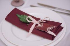Verziert mit grüner Blumenblatt- und Rosabogenserviette Stockfotos