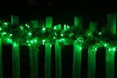 Verziert mit Weihnachtsgrünen Lichtern auf Zaun Stockbild