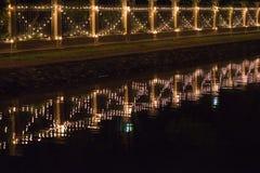Verzierte Birnen hingen an der Wand mit Reflexion des Kanals nachts Stockbild
