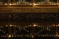 Verzierte Birnen hingen an der Wand mit Reflexion des Kanals nachts Stockfotografie