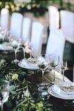 Verzierte elegante hölzerne Hochzeitstafel in der rustikalen Art mit Eukalyptus und Blumen, Porzellanplatten und Gläser stockbilder