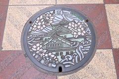 Verzierte geschnitzte Abwasserkappe auf der Straße von Osaka, Japan Lizenzfreies Stockbild