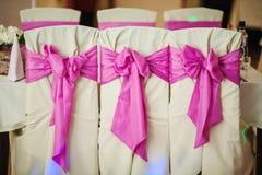 Verzierte Heiratsstühle mit Gewebe und rosa Bogen stockfoto