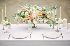 Verzierte Hochzeitstafel für zwei mit schöner Blumenzusammensetzung von Blumen, Gläser für Wein und Platten, im Freien, fein stockbild