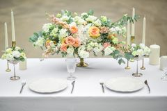 Verzierte Hochzeitstafel für zwei mit schöner Blumenzusammensetzung von Blumen, Gläser für Wein und Platten, im Freien, fein stockfotografie