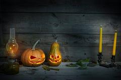 Verzierte Kürbise für ein Halloween auf einem mystischen Herbsthintergrund mit Kerzen und Gaslampe stockfotografie