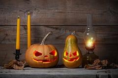 Verzierte Kürbise für ein Halloween auf einem mystischen Herbsthintergrund mit Kerzen und Gaslampe lizenzfreie stockfotos
