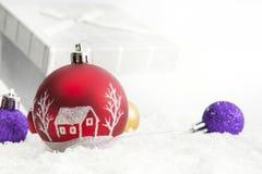 Verzierte Weihnachtsbälle und -geschenke auf weißem Hintergrund Stockbild