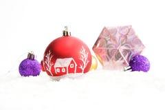 Verzierte Weihnachtsbälle und -geschenke auf weißem Hintergrund Stockfotos