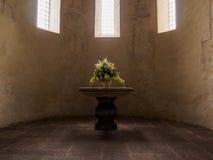 Verzierter Blumenvasenplatz auf dem Altar in der Schweizer Kirche Stockfotos