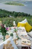 Verzierter eleganter Holztisch in der rustikalen Art mit Eukalyptus und Blumen, Porzellanplatten, Gläser, Servietten und Tischbes stockbilder