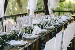 Verzierter eleganter Holztisch für ein Hochzeitsfest im Gazebo in der rustikalen Art mit Eukalyptus und Blumen, Porzellanplatten lizenzfreie stockfotos