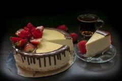 Verzierter Erdbeerkäsekuchen mit einer Tasse Tee und Erdbeeren lizenzfreie stockfotos