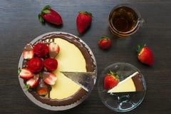 Verzierter Erdbeerkäsekuchen mit einer Tasse Tee und Erdbeeren stockfotos