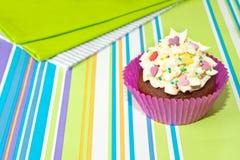 Verzierter kleiner Kuchen auf stripy Hintergrund Stockbild