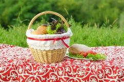 Verzierter Picknickkorb und -platte, Brötchen und Bündel Basilikum und Salat, grüne Landschaft Stockfotos