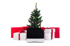Verzierter Weihnachtsbaum, Geschenkboxen und Laptop auf weißem backgro Stockbilder