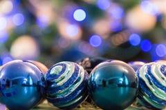Verzierter Weihnachtsbaum mit Blaulichtern Weihnachtsbälle im Vordergrund Unscharfes Bild eines Weihnachtsbaums im Hintergrund Lizenzfreies Stockbild