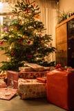 Verzierter Weihnachtsbaum mit Christbaumkugeln, Kerzenlicht und Geschenken stockbild