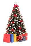 Verzierter Weihnachtsbaum mit Geschenken und Beuteln Stockbilder