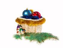 Verzierter Weihnachtskorb mit Weihnachtsspielwaren und -lametta Lizenzfreie Stockfotografie