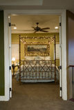 Verziertes Bett durch offene Türen Lizenzfreie Stockbilder