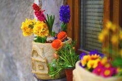Verziertes Fensterbrett mit Frühlingsblumen in den Töpfen lizenzfreie stockbilder