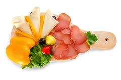 Verziertes Lebensmittel auf hölzerner Platte - Käse, Salami, Prosciutto lizenzfreie stockbilder