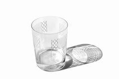 Verziertes transparentes Glas mit etwas Wasser lokalisiert Lizenzfreies Stockfoto