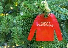Verzierung auf einem Weihnachtsbaum in Form eines roten Pullovers mit Aufschrift frohen Weihnachten stockfotografie