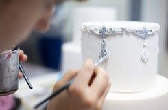 Verzierung der Hochzeitstorte, die durch Bürste färbt lizenzfreies stockfoto
