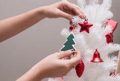 Verzierung des Baums der weißen Weihnacht mit rotem Stern, des kleinen grünen Baums und der roten Glocke Lizenzfreies Stockbild