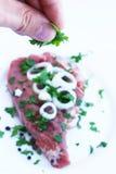 Verzierung des frischen Rindfleisches mit Grüns Lizenzfreie Stockfotografie