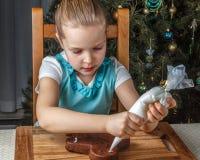 Verzierung des kleinen Mädchens des Weihnachtslebkuchenplätzchens stockfotos