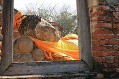 Verzierung: stützende Buddha-Statue hinter Fenster Stockbild