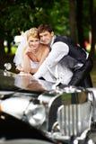 Verzorg adn bruid over retro limousine Stock Afbeelding