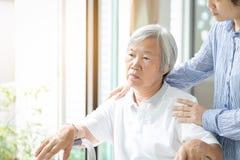 Verzorger Aziatische dochter of jonge verpleegster die zich achter de hogere vrouw bevinden die venster met hand op oudere womanâ royalty-vrije stock fotografie