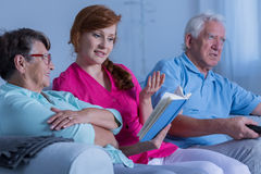 Verzorger die aan bejaarde lezen stock afbeeldingen