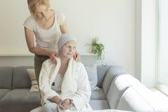 Verzorger thuis ondersteunend zieke hogere vrouw met borstkanker tijdens behandeling stock fotografie
