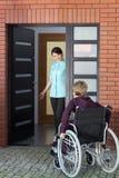 Verzorger uitnodigende vrouw op rolstoel aan verpleeghuis Stock Fotografie