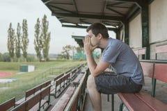 Verzweiflung und deprimierter Mann sitzt auf Bank am Stadion Stockbild