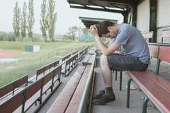 Verzweiflung und deprimierter Mann sitzt im Stadion Alleines und Einsamkeitskonzept Stockbild