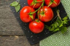 Verzweigen Sie sich mit fünf reifen roten Tomaten Wassertropfen auf reifen Früchten Grünblätter und -stamm Lizenzfreies Stockfoto