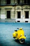 Vespa amarilla en plaza Imagen de archivo