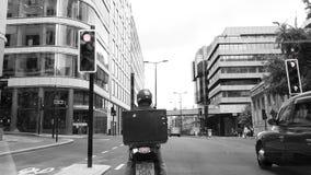 Vespa de la entrega del conductor en Londres blanco y negro